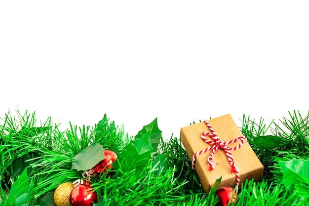 Kerstboomtakken met ballen en handgemaakte gift van kraft-inpakpapier op wit wordt geïsoleerd dat