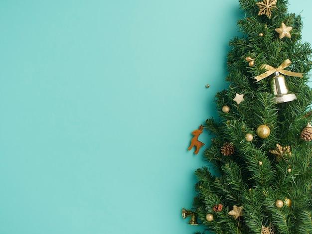 Kerstboomtakken met gouden kerstballen, sterren, dennenappels op lichtblauwe achtergrond
