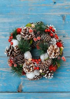 Kerstboomtakken met kegels op een donkere houten plank tegen een grijze betonnen muur.