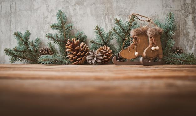 Kerstboomtakken met kegels op een houten plank tegen een grijze betonnen muur.