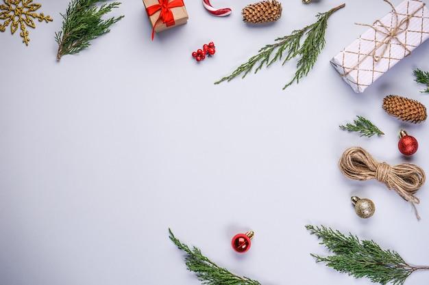 Kerstboomtakken met kerstversiering en geschenken op grijs met copyspace, plat leggen.