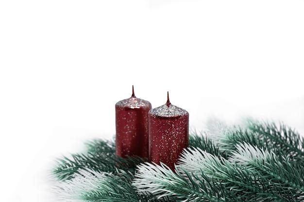 Kerstboomtakken met sneeuweffect en rode kaarsen