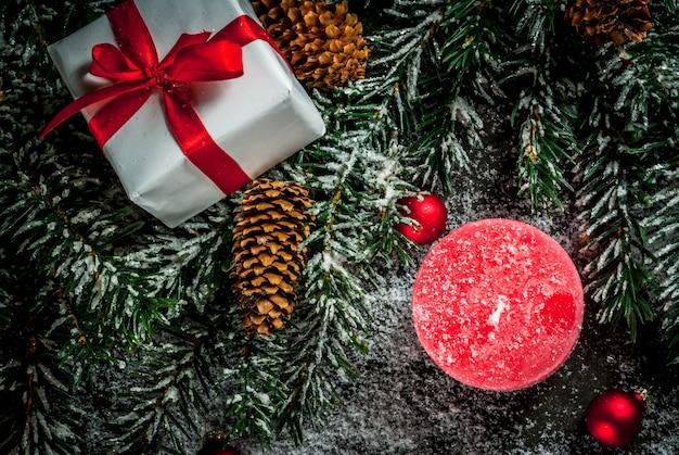 Kerstboomtakken met sneeuweffect met feestelijk rood lint, denneappels, giftdozen en kaarsen, op donkerblauwe achtergrond