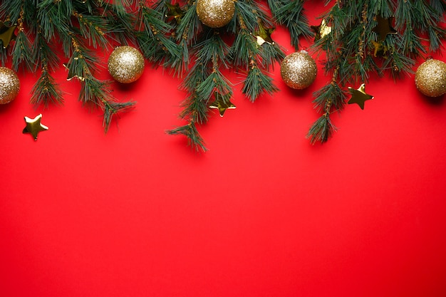 Kerstboomtakken met speelgoed op rood met copyspace