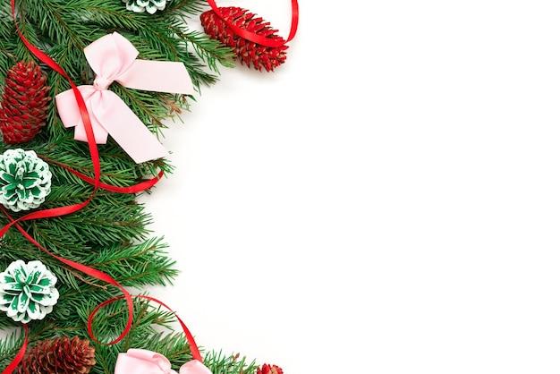 Kerstboomtakken met versieringen op een witte achtergrond.