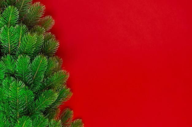 Kerstboomtakken op een rode achtergrond