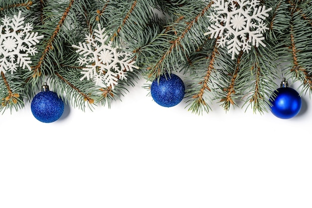 Kerstboomtakken versierd met sneeuwvlokken en blauwe kerstballen