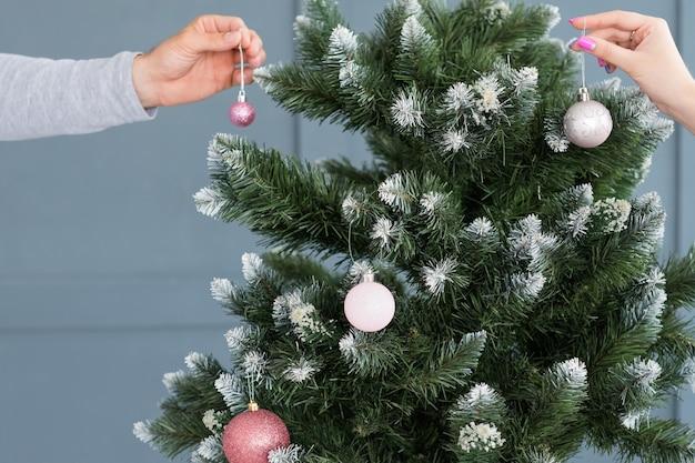 Kerstboomversiering. familievakantie tradities. handen die elegante balversieringen aan een groene spar hangen.