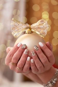 Kerstboomversiering in de handen van een vrouw. manicure op handen in nieuwe jaarstijl.