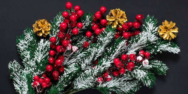 Kerstboomversiering op een donkere achtergrond. groene dennentakken met sneeuw, gouden dennenappels en rode hulstbessen.