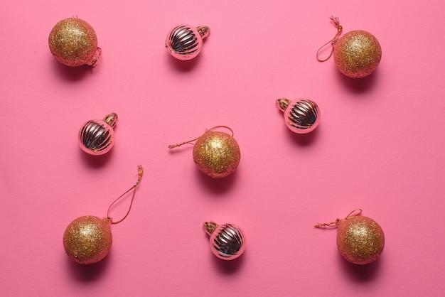 Kerstboomversieringen in de vorm van gouden ballen liggen op een roze achtergrond, bovenaanzicht. kerstmis en nieuwjaar concept