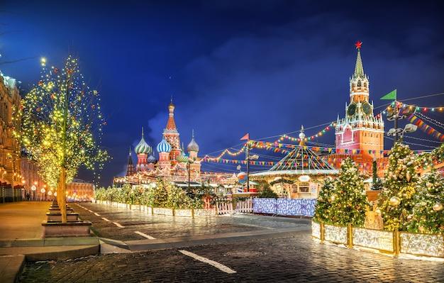 Kerstboomversieringen op het rode plein, koepels van de st. basiliuskathedraal en de spasskaya-toren op een winternacht
