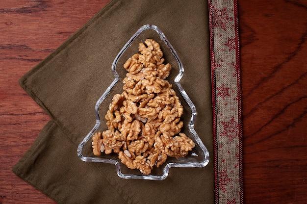 Kerstboomvormige schaal vol noten. bovenaanzicht. ruimte kopiëren.
