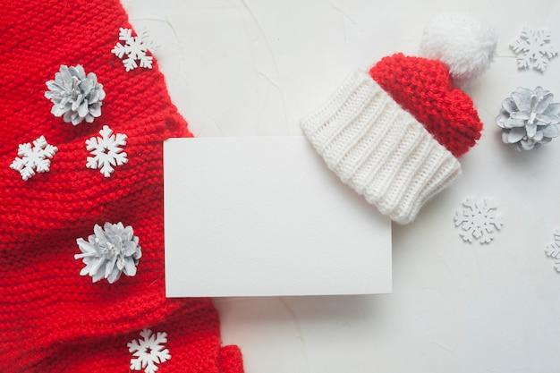 Kerstbrief aan de kerstman of wenskaart met rode gebreide sjaal en muts