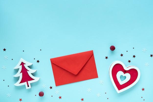 Kerstbrief met rode en witte versieringen op pastelblauw oppervlak, bovenaanzicht, kopie ruimte. kerst samenstelling. prettige kerstdagen en gelukkige feestdagen wenskaart, frame, banner, plat leggen
