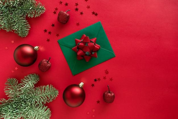 Kerstbrief met wenskaart en gefeliciteerd, kerstboomtakken, kerstballen, glitterdecoraties op rood oppervlak. vrolijk kerstfeest en gelukkig nieuwjaar concept.