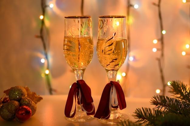 Kerstbril versierd met rode linten op de achtergrond van een lichtgevende slinger in oranje.