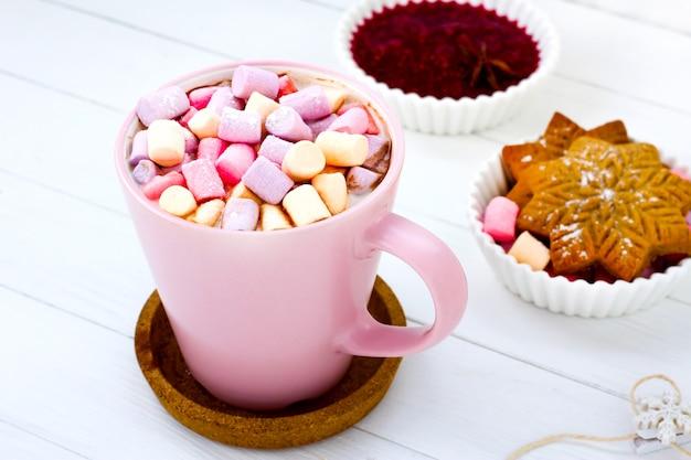 Kerstcacao marshmallow roze kop en gemberkoekje witte houten tafel frambozenjam