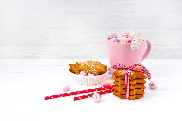 Kerstcacao met marshmallow in een roze kop en gemberkoekje op een houten tafel