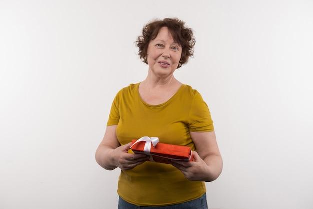 Kerstcadeau. blije oudere vrouw die een cadeau vasthoudt terwijl ze het voor kerstmis ontvangt
