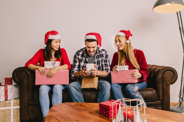 Kerstcadeau concept met drie vrienden op de bank