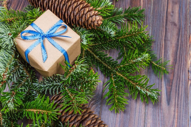 Kerstcadeau doos op de houten tafel, vuren tak, dennenappels, frame, bovenaanzicht