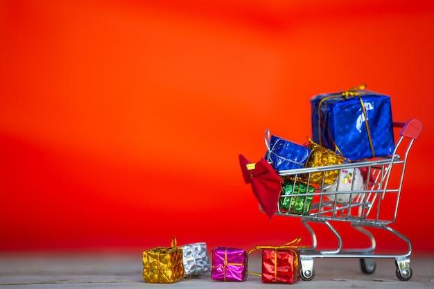 Kerstcadeau dozen in verschillende kleuren geplaatst in een winkelwagentje