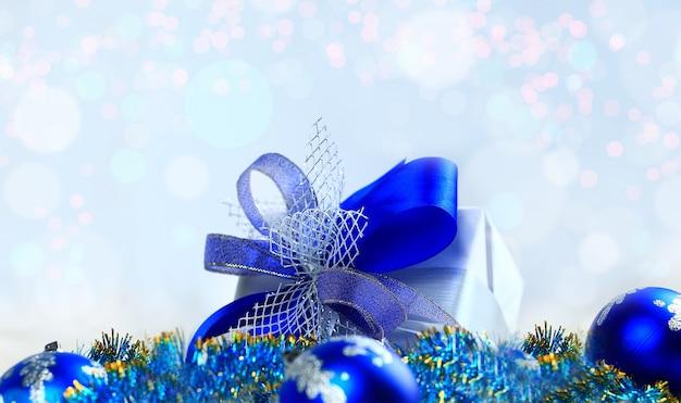 Kerstcadeau en blauwe ballen op witte achtergrond.