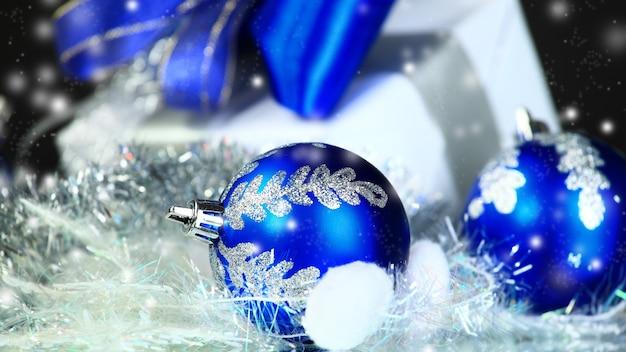 Kerstcadeau en blauwe ballen op zwarte feestelijke achtergrond. foto met kopieerruimte