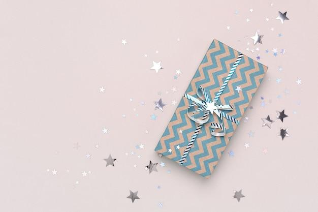 Kerstcadeau en confetti op beige achtergrond met kopie ruimte.