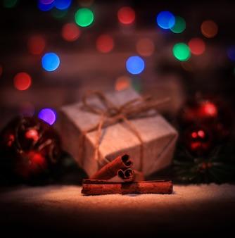 Kerstcadeau en kerstboomversieringen op de achtergrond van kerstverlichting.foto met kopieerruimte.