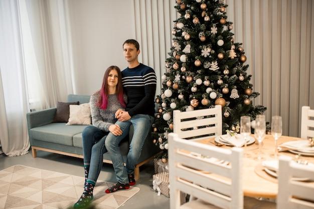 Kerstcadeau. gelukkige paar in de kerstmuts met kerst- en nieuwjaarsgeschenk thuis.