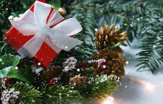 Kerstcadeau genesteld in decoraties met sneeuwlaag