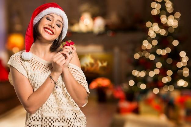 Kerstcadeau. glimlachende mooie vrouw in rode hoed en sjaal die met gesloten ogen voorstelt wat in de giftdoos, over kerstmisachtergrond is