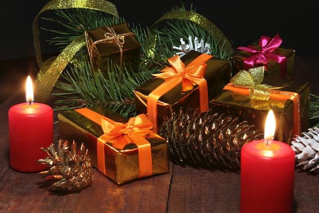Kerstcadeau goud, rode doos met gouden kleur boog en kaarsen.