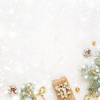 Kerstcadeau, groene twijgen en gouden versieringen op besneeuwde witte achtergrond.