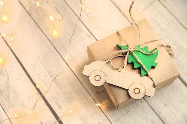Kerstcadeau in ambachtelijk papier met houten speelgoed op witte achtergrond met lichtgevende slinger