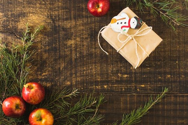 Kerstcadeau in de buurt van conifeertakjes en appel