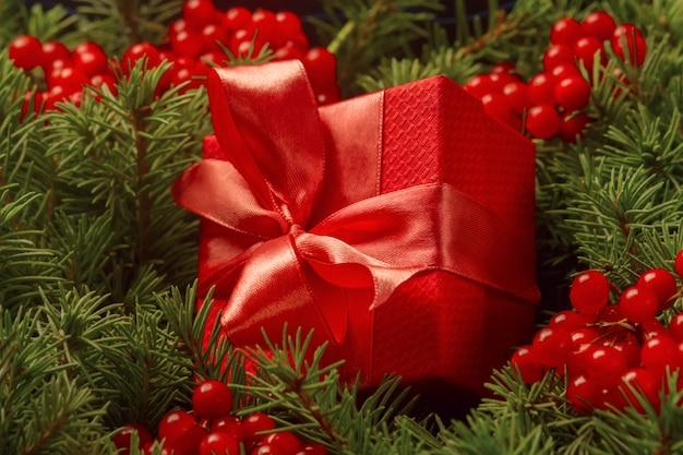 Kerstcadeau in een rode geschenkdoos met een koraal lint ondergedompeld in de naalden van een kerstboom.