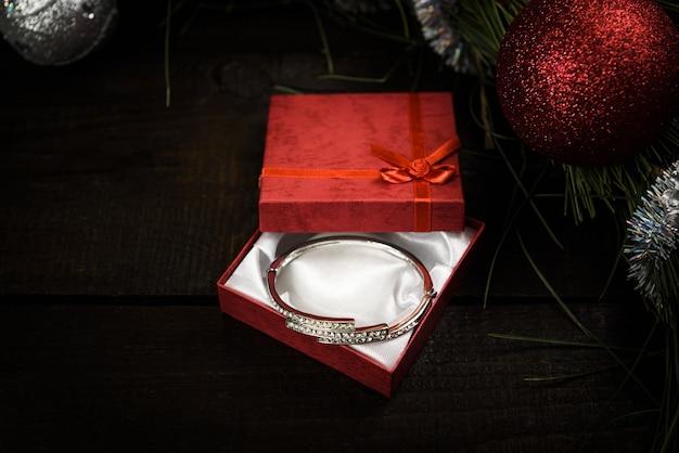 Kerstcadeau in rode doos met rood lint op houten ondergrond, omgeven door een kerstkrans