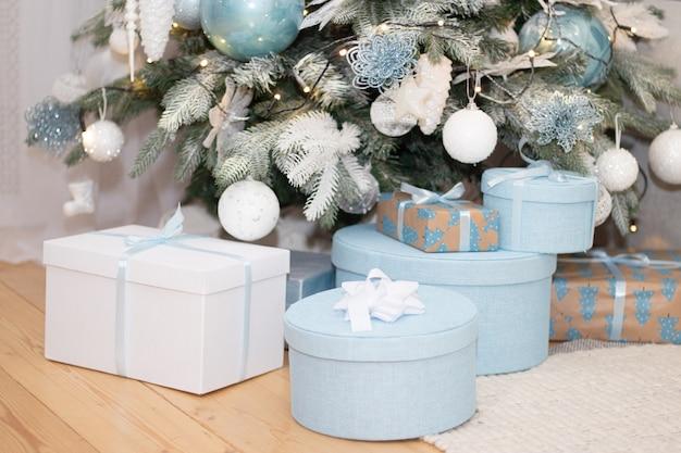 Kerstcadeau is onder de boom. nieuwjaar en kerstmis. gift. magie. verpakt geschenk. mooi pakket. buig op het pakket.