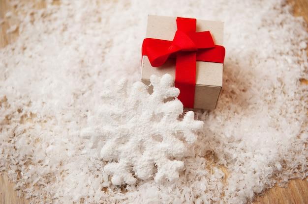 Kerstcadeau kraftpapier en een sneeuwvlok in de sneeuw