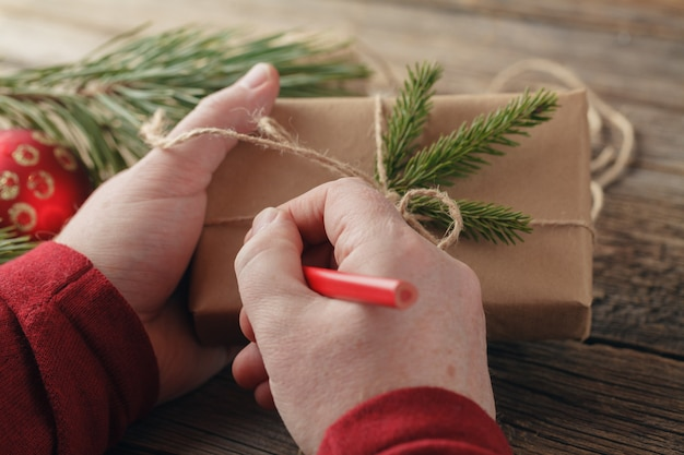 Kerstcadeau. mannelijke handen met nieuwjaar aanwezig. verpakte geschenken en rollen, werkplaats voor het maken van handgemaakte decoraties.