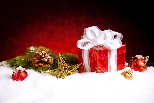 Kerstcadeau met decoraties op sneeuw