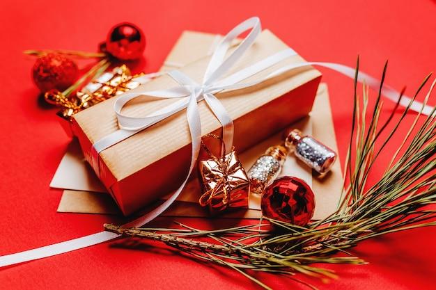 Kerstcadeau met fir branch en speelgoed op rood geïsoleerd.