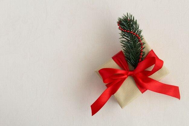 Kerstcadeau met rood lint op de beige textielachtergrond. bovenaanzicht. ruimte kopiëren.