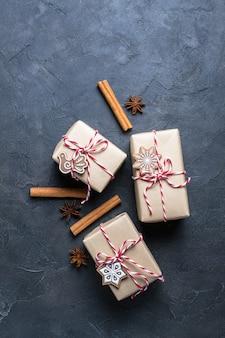 Kerstcadeau of huidige doos verpakt in kraftpapier met decoratie op donker. plat leggen