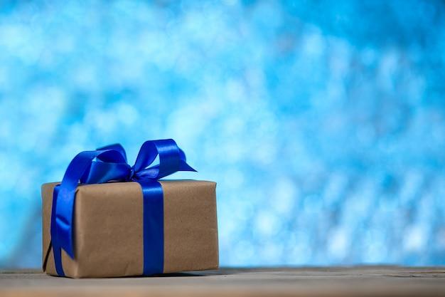 Kerstcadeau of nieuwjaar met een blauw lint op een rustieke houten tafel op een nacht blauwe bokeh