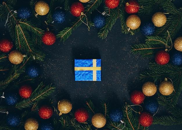 Kerstcadeau op een zwarte achtergrond met sparren en bovenaanzicht speelgoed. bovenaanzicht