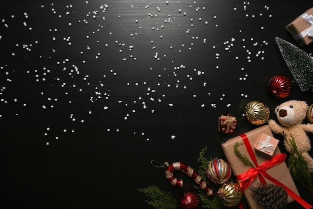 Kerstcadeau, teddybeer en sparren takken op zwarte achtergrond.